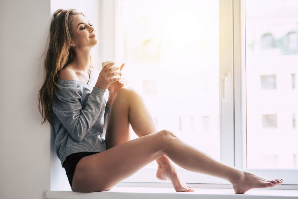 Woman contently sitting in window