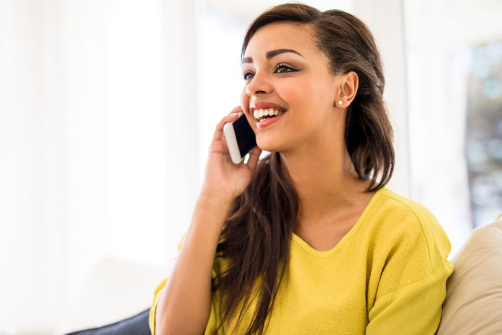 woman hearing big news over the phone