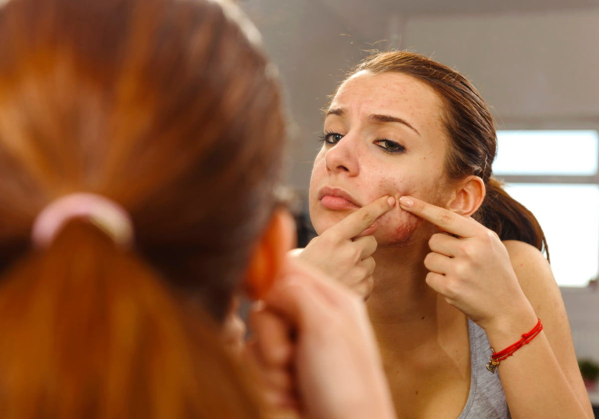 Teenage girl concerned about skin issues in the mirror before dermatologist